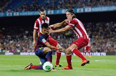 Neymar of FC Barcelona duels for the ball with Mario Suarez (L) and Filipe Luis of Atletico de Madrid during the Spanish Super Cup second leg match between FC Barcelona and Atletico de Madrid at Nou Camp on August 28, 2013 in Barcelona, Catalonia.