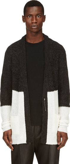 Long sleeve knit cardigan in black and white.  Bouclé knit at upper half with cable knit panels detail. Ribbed cuffs and hem. Oversize safety pin closure at front. Tonal stitching.