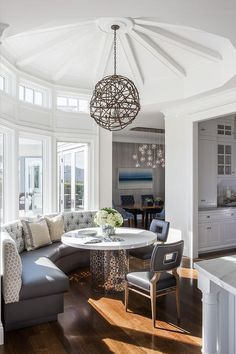 Round breakfast room features a tall ceiling lined with a driftwood pendant illuminating a wall of curved windows lined with a gray leather curved dining banquette facing a Jonathan Adler Nixon Dining Table and dark gray leather cut out back dining chairs.
