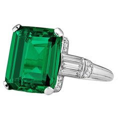 Important Art Deco Colombian Cushion Cut Natural Emerald Ring , circa 1925-30. The important 7.10 carat natural classic Columbian emerald has an AGL certification # CS/51044 and is truly hypnotic. An original period styled handmade platinum mounting incorporates 12 baguette cut diamonds weighing approximately .025-.06 carats each, 26 old European cut and single cut diamonds weighing between .002-.005 carats, all with millgrain and engraved detail.  Via 1stdibs.