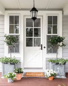 A beautiful gray home with white front door. The galvanized planters are filled with topiaries and the terra cotta pots are filled with white petunias. #frontporch #porchdecor