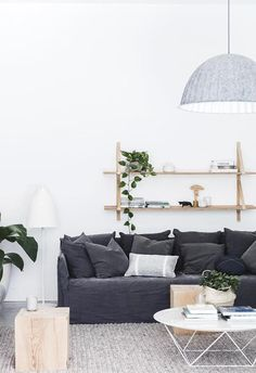A pale grey Muuto pendant light hangs over a textured neutral rug in the living room. A charcoal couch adds contrast to the white walls and hanging shelves. Coastal Living Rooms, Home And Living, Living Room Decor, Living Area, Style At Home, Charcoal Couch, Charcoal Sofa Living Room, Beach House Decor, Bedroom Ideas