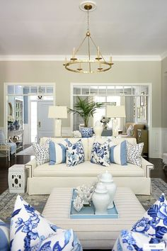 Gorgeous summer living room decorated with blue and white pillows, coral accents and palms.