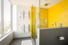 Palette Profile - Yellow, Gray, and White Interiors // Surrounded by white walls and gray flooring, the yellow tiles are confined to the shower to prevent the color from completely dominating the space.