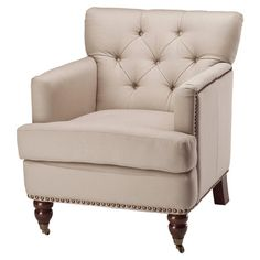 Cotton-upholstered tufted arm chair in beige with a wood frame and nailhead trim.   Product: ChairConstruction Material...