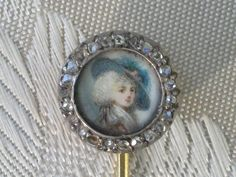 This Georgian (c 1790-1795) miniature stick pin, featuring the portrait of an unknown woman, is set in gold and surrounded by twenty three diamonds.    Dressed a l'anglaise the woman in the portrait is painted on ivory, and considering its size of 1/2 an inch in diameter the craftsmanship of the portrait artist is superb. Much of this would have been painted with a single hair brush.  Private collection
