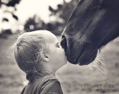 Precious horse kiss. Little kid getting right in there for some horse loving!