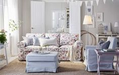 A light living room furnished with a three-seat sofa with a floral pattern and a…