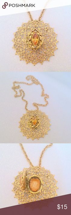"""Amber Rhinestone Filigree Perfume Locket Necklace This lovely vintage perfume locket necklace is done in a gold tone filigree lace design with a marquis shaped amber rhinestone at the center. Locket still has some of the perfume inside though it is pretty dried up! The chain on the necklace measures 24"""" in length and the locket measures 2 1/2"""" in diameter and can also be used as a brooch. In beautiful condition! Unbranded Jewelry Necklaces"""