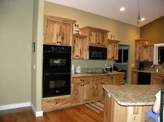 Kitchen Elegant Unfinished Wood Hickory Cabinets With White Ceiling Lighting Over Brown Granite