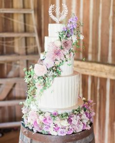 Buttercream frosting enrobed the wedding cake—which was made of tiers of lemon damson plum and Mexican hot chocolate. Displayed on a wine barrel during the reception, fresh flowers and a custom topper by Laura Hooper Calligraphy incorporating the couple's monogram adorned the confection.