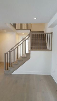 White Oak stair constructed with closed risers, closed stringer both sides Railing system constructed with 2'' square handrail, 3'' square plain posts and 1/2'' square black metal spindles Stained and finished to clients selected colour #AffordableInteriorDesignChicago