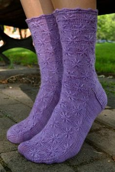 Inspired by the dainty lilac flower and starting with a scalloped edge, these socks are knit from the cuff down and embellished with flowers created by using wrapped and slipped stitches.