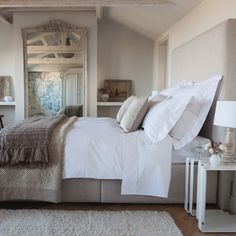 Serene bedroom with floor length mirror, light gray walls, gray upholstered headboard, white bedding and gray throw at the foot of the bed.