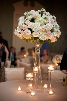 The combination of a high rose and hydrangea arrangement with varying heights of candles is such a classy look!