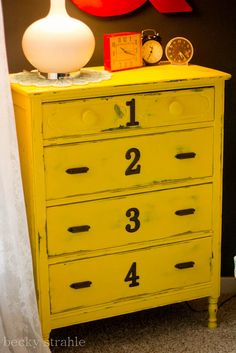 This dresser makes my heart go pitter pat!  Black dresser that was spray painted yellow and scuffed to reveal this gorgeousness!  Added numbers and new knobs.  from Farmgirl Paints