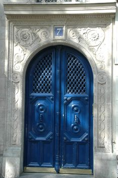 A French blue set of doors surrounded by a stone archway with a simple swirl design.  Unknown location.