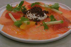 Dit koud voorgerecht presenteert feestelijk en kleurrijk. Gerookte zalm blijft populair bij velen en met een kleine moeite pimp je de plakjes vis tot een bijzonder fris bordje plezier, met partjes fruit en krokante kruimels compact roggebrood. Denk er wel tijdig aan om de yoghurt te laten uitlekken tot een smeuïge ingedikte
