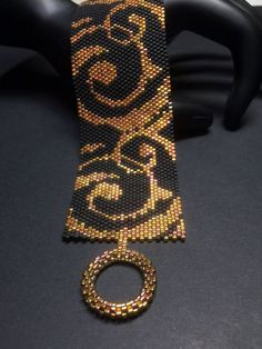 This is a Beautiful Beaded Peyote Elegance Bracelet. The dimensions for this bracelet are approximately 1.59in-inch width x 6.92in-inch length when using 11/0 Delica seed beads. There is a total of 2 bead colors, with a total bead count of 3000 beads (30 beads by 100 beads). This