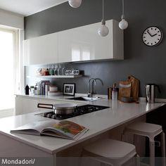 Mit der grauen Wandfarbe und den schnörkellosen Schränken, Arbeitsflächen und Barhockern in Weiß wirkt diese Küche angenehm unaufgeregt und übersichtlich. …