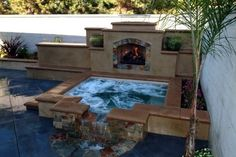 hot tub with a waterfall & fireplace. love.