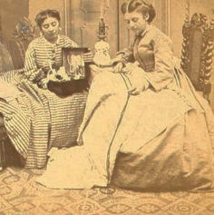 Women posed with their sewing and an oil lamp. They seem to be adding decorative tape to a skirt, a military look popular during the Civil War.
