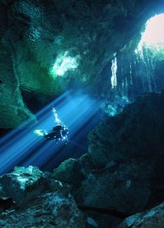 Diver passes through ray of light in Taj Mahal cenote