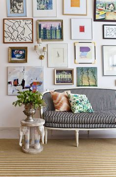 This unique gallery wall does not shy away from color or pattern, but embraces them both in subtle ways. The black and white stripes of the couch keep things orderly, while dashes of color like purple and red keep things interesting. Shop beautiful high-quality art prints to keep your space inspired from Redbubble.com.