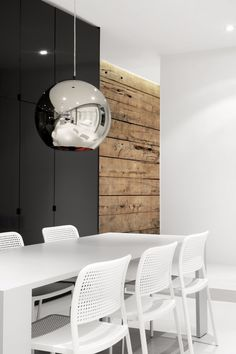 Opposite attracts: Rustic wood on wall and shiny silver pendant lighting.  By Designer Tom Dixon.