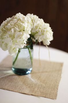 I went to an administration meeting and loved this idea.. very simple, but elegant Simple hydrangea centerpiece in a seaglass vase with burlap