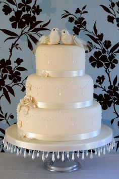 Not a fan of the birds on the top or the flowers, but like the ribbon and chandelier look on each tier