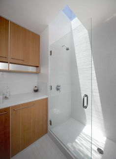 The subway tile-lined bathroom was kept as simple as possible, with Hansgrohe fixtures and cabinets made of vertical-grain Douglas fir above a top-mounted Duravit sink. Since installing a window was unfeasible given the bathroom's proximity to other properties, Storey added a skylight over the shower.
