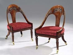 A Pair of Regency Period Curricle Chairs.  English, Circa 1815.  Having spoon shaped backs with carved anthemions to the splats and carved volutes to the arms, this pair of chairs have been decorated to resemble rosewood and are superbly proportioned. The chairs stand on turned and reeded legs to the front and swept back legs to the back, all retaining their original brass castors which have been cleaned and lacquered.