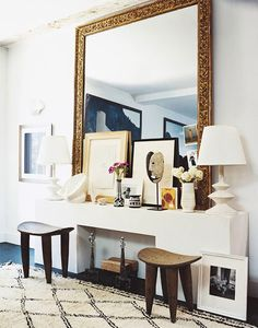 a modern take on the fireplace uses matching stools and a large ornate gold mirror for interest
