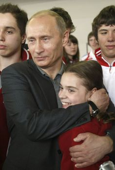 Russia's Prime Minister Vladimir Putin hugs figure skater Adelina Sotnikova, 12, as they pose for a picture at a special school for training potential Olympic candidates in Moscow May 7, 2009. REUTERS/Denis Sinyakov (RUSSIA POLITICS SPORT IMAGES OF THE DAY) - RTXETTV