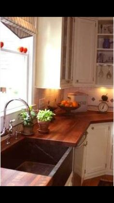 Love the butcher block counter top and farm sink in this kitchen
