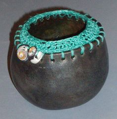 You can add other materials to pinch pots after they have been fired. Just make sure you plan ahead and make the necessary holes or notches. You could use yarn, string, beads, paper, raffia, or whatever you can imagine!
