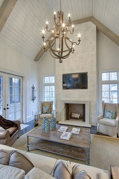Floor to Ceiling Fireplace w/ TV mounted above; don't love the treatment they used on the fireplace but a nice design.
