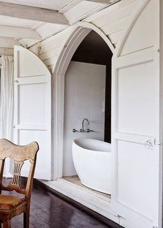 Love this bath tucked away behind gorgeous doors!