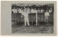 Anonymous | Groepsportret van werknemers in Moengo., Anonymous, 1929 - 1930 | Briefkaart van een foto. Een rij mensen achter een schutting. Twee mannen staan ervoor. Rechts poseert een Creoolse vrouw. Achterzijde schrijflijnen.