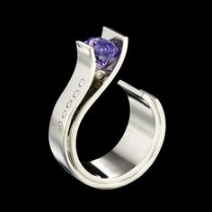 A modern engagement ring design by Adam Neeley.  In Fiore sapphire ring a gemstone blooms forth from graceful petals of gold. This ring features a distinctive purple sapphire set in white gold with accent diamonds.