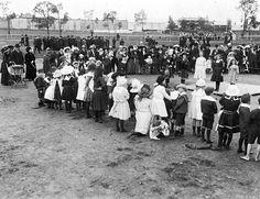 Presentations at the Rainbow sports day, circa 1915 - Museum Victoria. Four young girls stand on a platform and a piper stands beside them, probably Yurunga Homestead in the background.