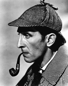 Peter Cushing as the iconic detective Sherlock Holmes. Complete with deerstalker and pipe
