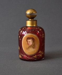 Early ruby glass perfume bottle. Hand painted applied cartouche of a girl