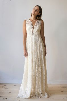 A free-spirited gown for the wild at heart. Genevieve is made from a very special cotton embroidered tulle with a Beaux Arts floral motif. Neckline finished with scalloped edges plunges to a raised fitted waist. Gently gathered skirt is finished with a luxurious scalloped hem. Satin ties fin