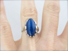 Deep, midnight blue lapis lazuli is the perfect contrast to the bright white gold that makes up the frame of this vintage cocktail ring. We love the way the light catches in the faceted leaves that form a halo around the stone! Metal: 10 Karat White Gold Gem: Lapis Gem Measurements: 18 x 9 mm oval Marks: Stamped 925 on the inside of the shank, Size of Ring: 5 1/2 Sizing Availability: This piece can be sized up or down by our shop for a nominal fee. Please contact us for details. Marks: ...