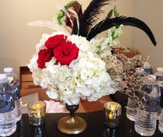 1920s Gatsby Centerpiece: Gold footed pedestal filled with White Hydrangea, White Snapdragons, German Statice and red roses accented with black feathers for a Gatsby 1920s Speakeasy theme   by Andrea Layne Floral Design (www.andrealaynefloraldesign.com)