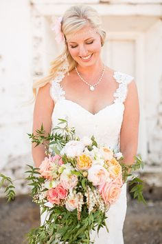 A cascading bouquet of peach and cream garden roses and greenery | @stewartuy | Brides.com