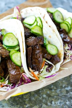 This recipe for Korean BBQ Tacos is marinated and seared beef layered with cabbage slaw and marinated cucumbers, all tucked into warm flour tortillas.