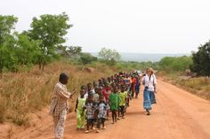 Peggy Hahn, Assistant to the Bishop for the TX-LA Gulf Coast Synod walks alongside school children in the Central African Republic ~ 2012